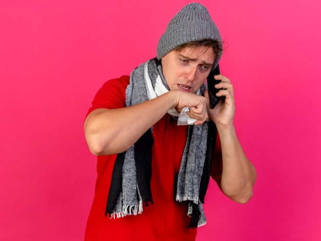 Schwacher junger hübscher blonder kranker mann, der wintermütze und schal trägt, die am telefon sprechen serviette halten hand nahe mund suchen lokalisiert auf purpurrotem hintergrund mit kopienraum