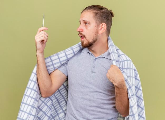 Schwacher junger hübscher slawischer kranker mann, der in kariertes halten und betrachten des thermometers lokalisiert auf olivgrünem hintergrund eingewickelt ist