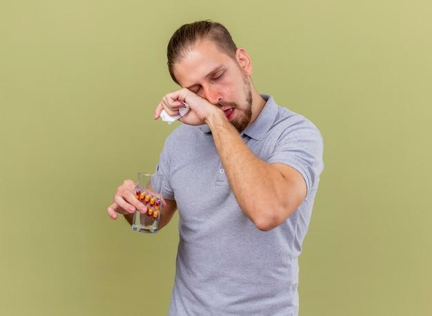 Schwacher junger hübscher slawischer kranker mann, der packung kapseln glas wasser und serviette berührt gesicht mit geschlossenen augen hält, die auf olivgrüner wand mit kopienraum lokalisiert werden