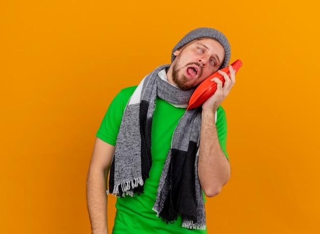 Schwacher junger hübscher slawischer kranker mann, der wintermütze und schal berührendes gesicht mit den heißen augen des heißen wassersacks trägt, die auf orange wand mit kopienraum isoliert werden