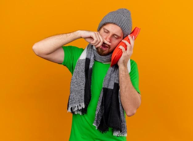 Schwacher junger hübscher slawischer kranker mann, der wintermütze und schal berührendes gesicht mit heißem wassersack trägt, der nase mit finger mit geschlossenen augen abwischt, lokalisiert auf orange wand mit kopienraum