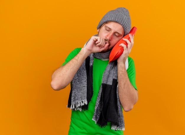 Schwacher junger hübscher slawischer kranker mann, der wintermütze und schal berührt gesicht mit heißem wasserbeutel hustend hält faust in der nähe des mundes mit geschlossenen augen isoliert auf orange wand mit kopienraum