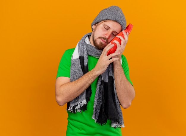 Schwacher junger hübscher slawischer kranker mann, der wintermütze und schal hält, die heißes wasserbeutel-berührungsgesicht mit ihm mit geschlossenen augen lokalisiert auf orange hintergrund mit kopienraum halten