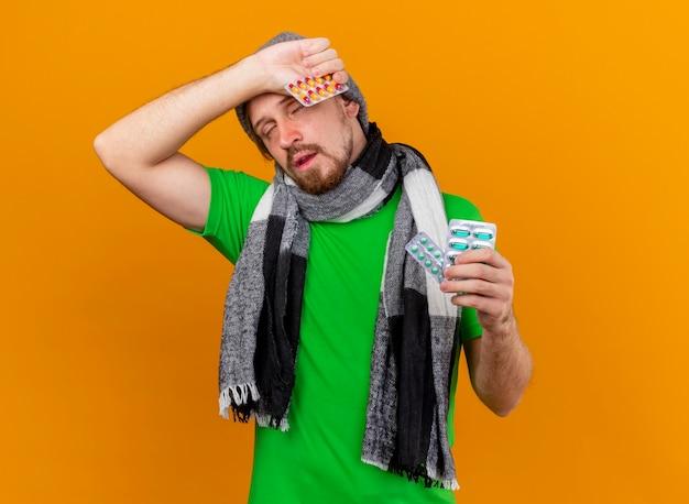 Schwacher junger hübscher slawischer kranker mann, der wintermütze und schal hält, die packungen der kapseln halten, die kopf mit geschlossenen augen berühren, lokalisiert auf orange wand mit kopienraum