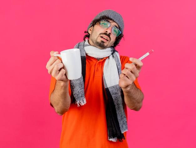 Schwacher junger kaukasischer kranker mann, der brille wintermütze und schal trägt, die tasse und thermometer in richtung kamera lokalisiert auf purpurrotem hintergrund ausdehnen