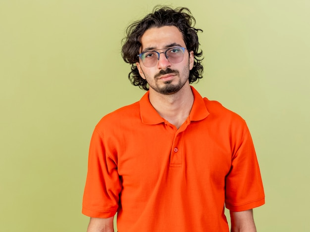 Schwacher junger kaukasischer kranker mann, der brillen trägt, die kamera lokalisiert auf olivgrünem hintergrund mit kopienraum betrachten