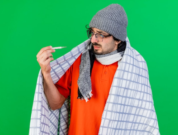 Schwacher junger kaukasischer kranker mann, der die wintermütze und den schal der brille trägt, die im karierten halten und im betrachten des thermometers lokalisiert auf grünem hintergrund eingewickelt sind
