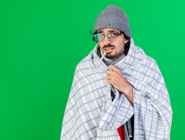 Schwacher junger kranker mann, der brille wintermütze und schal in plaid hält, die thermometer im mund hält, das front ergreifendes plaid lokalisiert auf grüner wand betrachtet