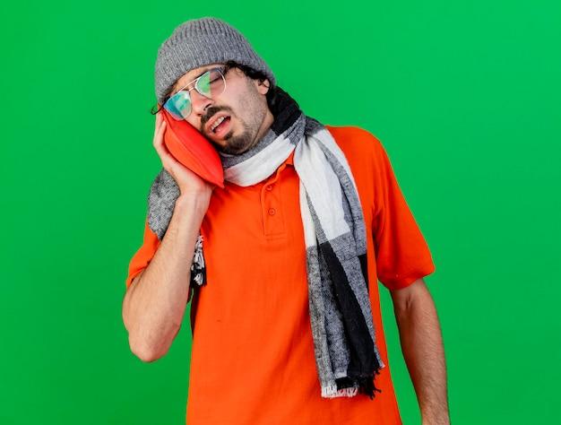Schwacher junger kranker mann, der brille wintermütze und schal trägt, die heißen wasserbeutel auf gesicht mit geschlossenen augen lokalisiert auf grüner wand mit kopienraum setzen