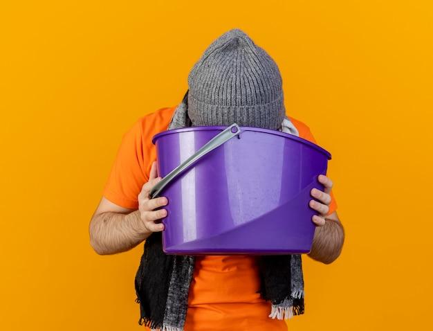 Schwacher junger kranker mann, der wintermütze mit schal hält, der plastikeimer hält und sich darin erbricht, isoliert auf orange