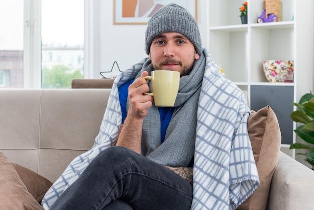 Schwacher junger kranker mann mit schal und wintermütze, der auf dem sofa im wohnzimmer sitzt und in eine decke gehüllt ist, die eine tasse tee mit blick auf die vorderseite hält