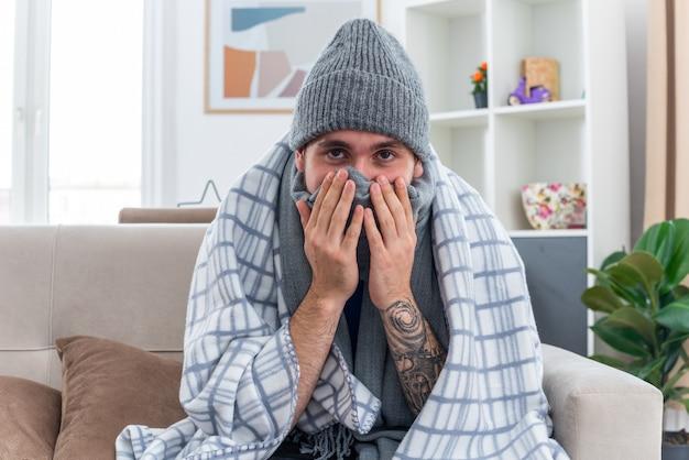Schwacher junger kranker mann mit schal und wintermütze, der auf dem sofa im wohnzimmer sitzt und in eine decke gehüllt ist, die mund und nase mit schal bedeckt und die hände auf dem gesicht hält und nach vorne schaut
