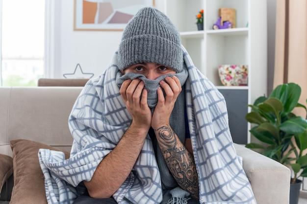 Schwacher junger kranker mann mit schal und wintermütze, der auf dem sofa im wohnzimmer sitzt und in eine decke gehüllt ist und die kamera betrachtet, die den mund mit schal bedeckt