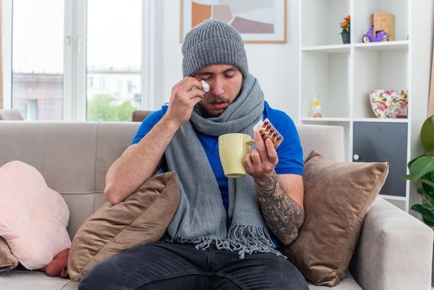Schwacher junger kranker mann mit schal und wintermütze, der auf dem sofa im wohnzimmer sitzt und pillenpackungen und eine tasse tee hält, die das auge mit geschlossenen augen abwischt