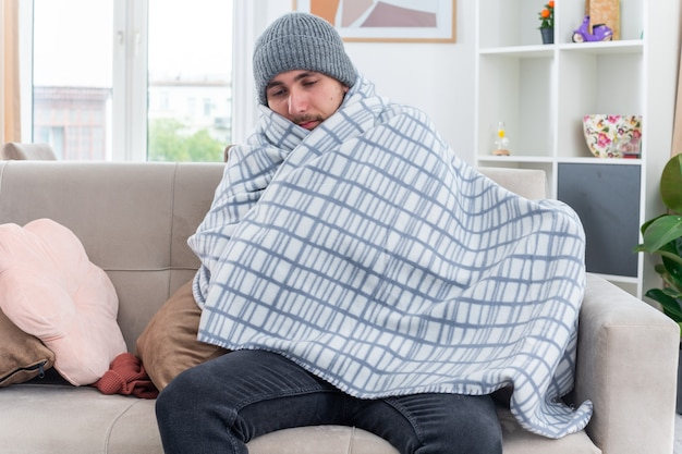Schwacher junger kranker mann mit schal und wintermütze, der in eine decke gehüllt auf dem sofa im wohnzimmer sitzt und nach unten schaut