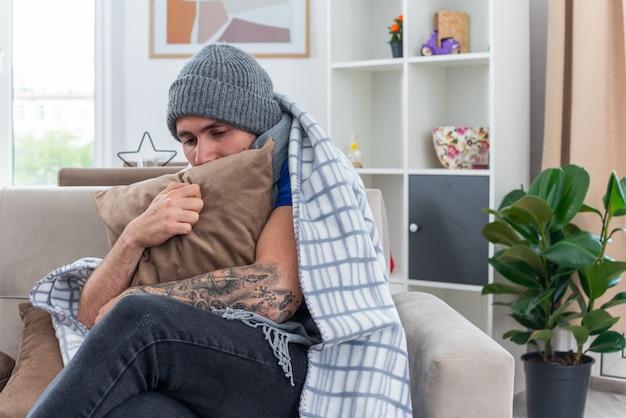 Schwacher junger kranker mann mit schal und wintermütze, der mit gekreuzten beinen auf dem sofa im wohnzimmer sitzt, eingewickelt in eine decke, die das kissen nach unten umarmt