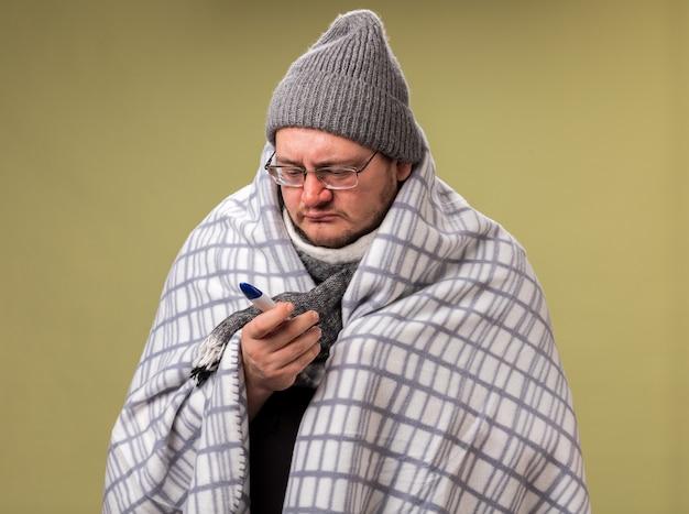 Schwacher kranker mann mittleren alters, der wintermütze und schal trägt, der in kariertes halten gewickelt ist und das thermometer isoliert auf der olivgrünen wand betrachtet