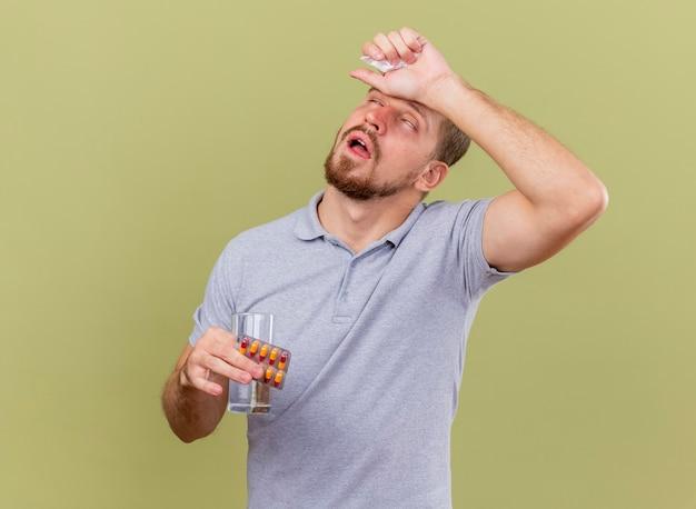 Schwacher und schmerzender junger hübscher slawischer kranker mann, der packung kapseln glas wasser und serviette hält hand auf kopf mit geschlossenen augen lokalisiert auf olivgrüner wand mit kopienraum