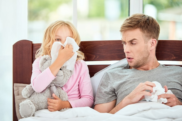Schwaches immunsystem junger vater und tochter, die an grippe oder erkältung leiden und laufende nasen haben
