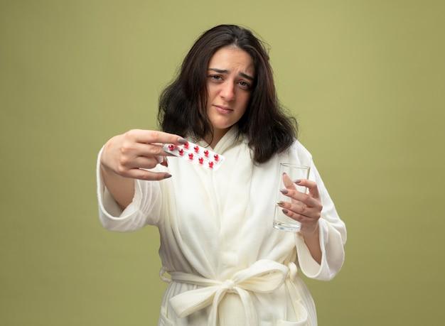 Schwaches junges kaukasisches krankes mädchen, das eine robe trägt, die packung der medizinischen pillen gegen kamera hält, die glas wasser hält, die kamera lokalisiert auf olivgrünem hintergrund mit kopienraum betrachtet