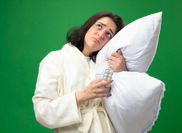 Schwaches junges kaukasisches krankes mädchen, das gewand umarmt, das kissen setzt, das den kopf auf ihn hält, der glas wasser und packung der medizinischen tabletten hält, die lokal auf grünem hintergrund suchen