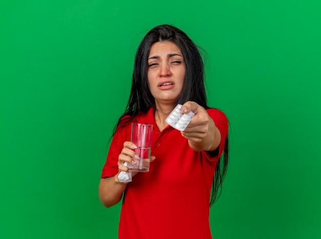 Schwaches junges kaukasisches krankes mädchen, das packung der tabletten glaswasser und serviette hält, die packung der tabletten in richtung kamera streckt kamera betrachtet auf lokalisiertem grünem hintergrund mit kopienraum