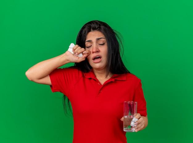 Schwaches junges kaukasisches krankes mädchen, das packung der tabletten glaswasser und serviettenberührungsgesicht mit geschlossenen augen lokalisiert auf grünem hintergrund mit kopienraum hält