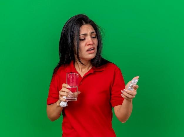 Schwaches junges kaukasisches krankes mädchen, das packung tablettenglas wasser und serviette hält, die tabletten lokalisiert auf grünem hintergrund mit kopienraum betrachtet