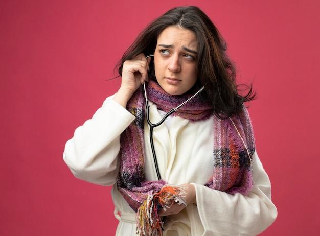 Schwaches junges kaukasisches krankes mädchen, das robe und schal und stethoskop trägt und seite betrachtet, die auf purpurroter wand lokalisiert
