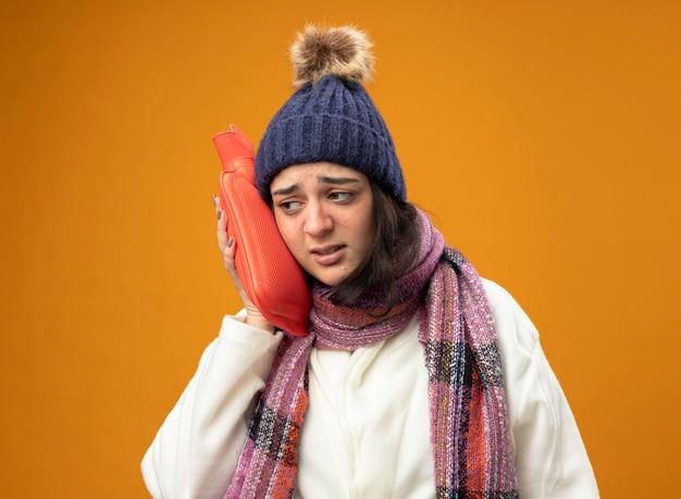 Schwaches junges kaukasisches krankes mädchen, das robe wintermütze und schal berührenden kopf mit heißem wassersack trägt, der seite lokalisiert auf orange hintergrund mit kopienraum betrachtet