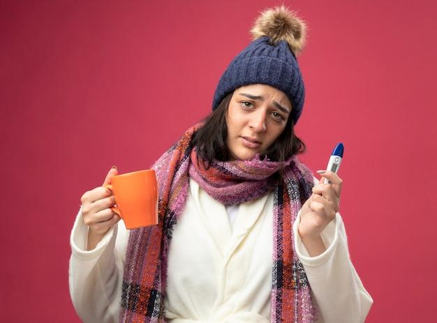 Schwaches junges kaukasisches krankes mädchen, das robe wintermütze und schal hält, die tasse tee und thermometer hält, die kamera lokalisiert auf purpurrotem hintergrund betrachten