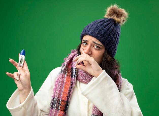 Schwaches junges kaukasisches krankes mädchen, das robe wintermütze und schal hält, die thermometerwischnase lokalisiert auf grüner wand halten