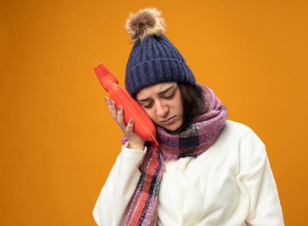 Schwaches junges kaukasisches krankes mädchen, das robe wintermütze und schal rührenden kopf mit heißem wassersack mit geschlossenen augen trägt, lokalisiert auf orange hintergrund mit kopienraum