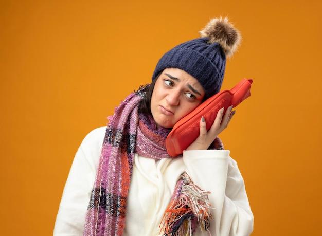 Schwaches junges kaukasisches krankes mädchen, das robe wintermütze und schal rührenden kopf mit heißem wassersack trägt, der seite lokalisiert auf orange hintergrund betrachtet