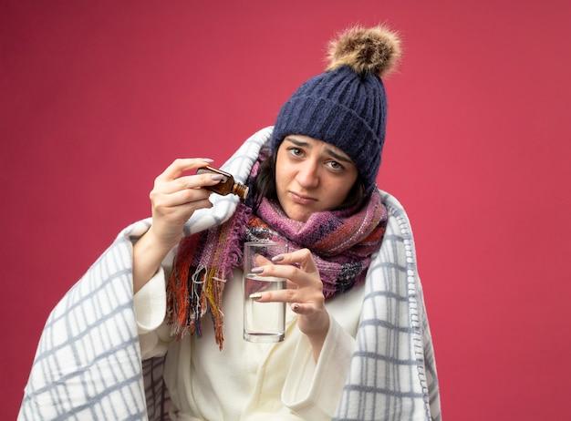 Schwaches junges kaukasisches krankes mädchen, das robe wintermütze und schal trägt, die im plaid eingewickelt werden, das medikament in glas des wassers isoliert, das auf purpurroter wand mit kopienraum isoliert wird