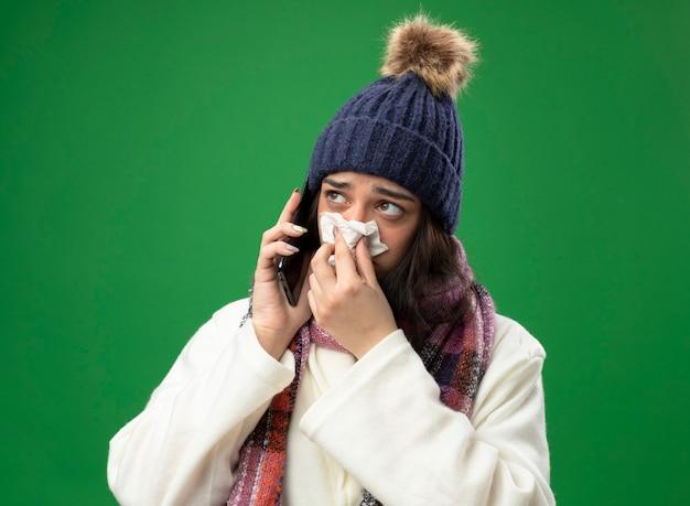Schwaches junges kaukasisches krankes mädchen, das robe wintermütze und schal trägt, spricht am telefon, das nase mit serviette abwischt, die seite lokalisiert auf grünem hintergrund betrachtet