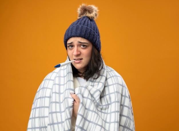 Schwaches junges kaukasisches krankes mädchen, das robenwintermütze wickelt, wickelte in plaid packendes plaid ein, das kamera mit thermometer im mund lokalisiert auf orange hintergrund mit kopienraum betrachtet