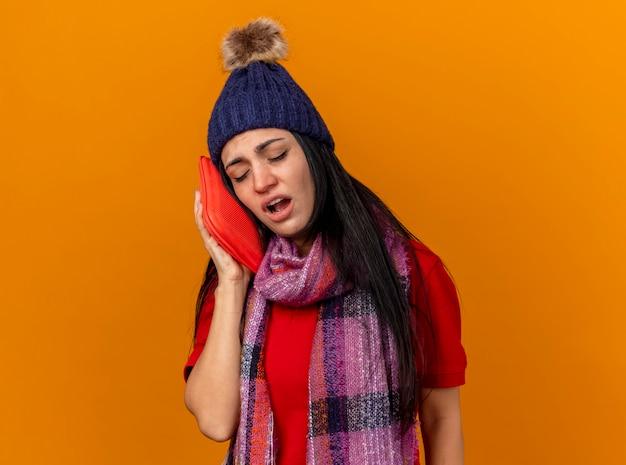 Schwaches junges kaukasisches krankes mädchen, das wintermütze und schal berührendes gesicht mit heißem wasserbeutel mit geschlossenen augen trägt, die auf orange wand mit kopienraum lokalisiert werden
