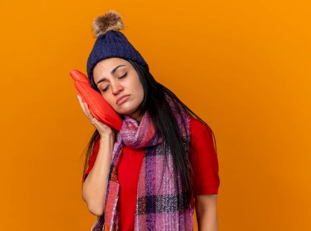 Schwaches junges kaukasisches krankes mädchen, das wintermütze und schal berührendes gesicht mit heißem wassersack mit geschlossenen augen trägt, lokalisiert auf orange hintergrund mit kopienraum