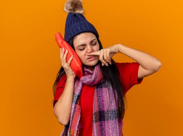Schwaches junges kaukasisches krankes mädchen, das wintermütze und schal berührendes gesicht mit heißem wassersack trägt, der nase mit finger mit geschlossenen augen abwischt, lokalisiert auf orange wand mit kopienraum