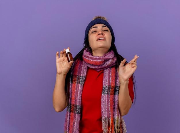 Schwaches junges kaukasisches krankes mädchen, das wintermütze und schal hält, das medikament im glas hält, macht glücksgeste mit geschlossenen augen lokalisiert auf lila hintergrund mit kopienraum