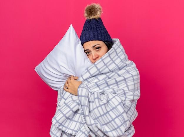 Schwaches junges kaukasisches krankes mädchen, das wintermütze und schal trägt, eingewickelt im karierten umarmenden kissen, das den kopf darauf setzt und kamera betrachtet, die auf purpurrotem hintergrund mit kopienraum isoliert ist
