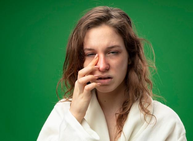 Schwaches junges krankes mädchen, das geradeaus schaut und weißes gewand trägt, das auge mit finger isoliert auf grün abwischt