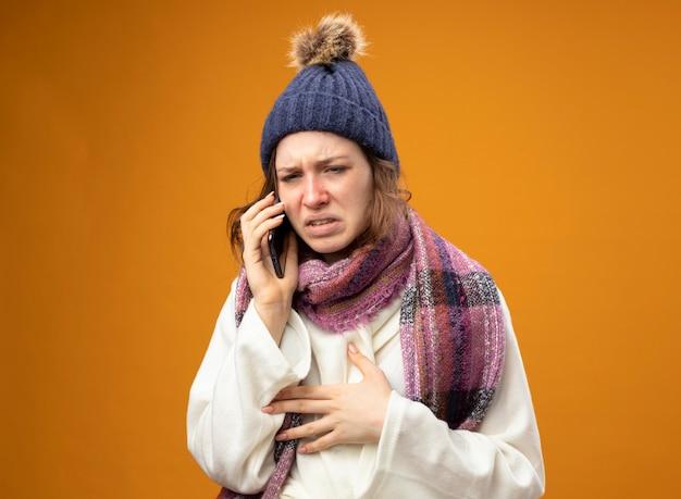 Schwaches junges krankes mädchen, das weiße robe und wintermütze mit schal trägt, spricht am telefon lokalisiert auf orange