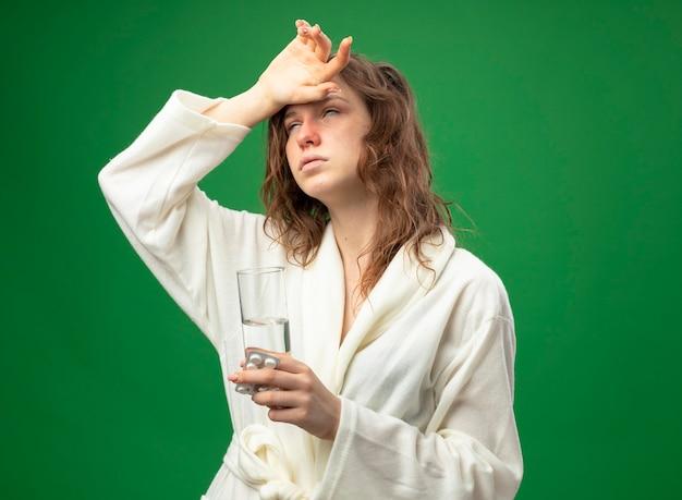 Schwaches junges krankes mädchen, das weißes gewand trägt, das glas wasser mit pillen hält und hand auf stirn lokalisiert auf grün setzt