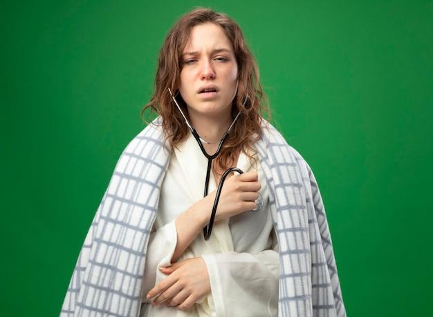 Schwaches junges krankes mädchen, das weißes gewand trägt, das in plaid eingewickelt ist, das ihren eigenen herzschlag mit dem auf grün isolierten stethoskop hört