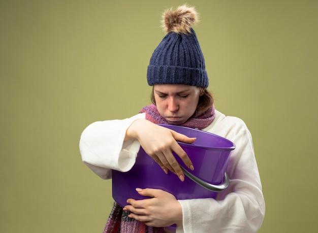 Schwaches junges krankes mädchen, das weißes gewand und wintermütze mit schal hält, der plastikeimer hält, der übelkeit lokalisiert auf olivgrün hält