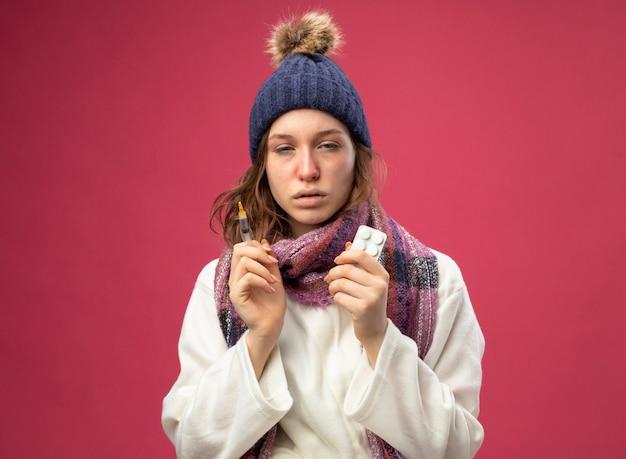 Schwaches junges krankes mädchen, das weißes gewand und wintermütze mit schal hält spritze mit pillen lokalisiert auf rosa trägt