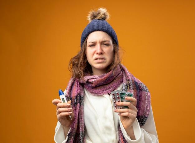Schwaches junges krankes mädchen, das weißes gewand und wintermütze mit schal hält thermometer mit pillen auf orange wand isoliert trägt