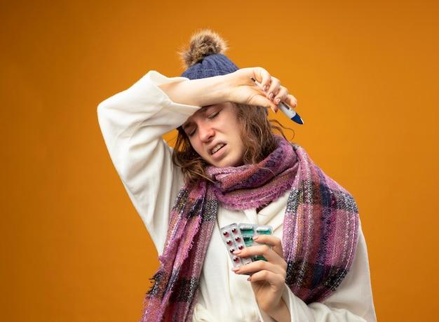 Schwaches junges krankes mädchen, das weißes gewand und wintermütze mit schal hält thermometer mit pillen hält arm auf stirn lokalisiert auf orange wand trägt